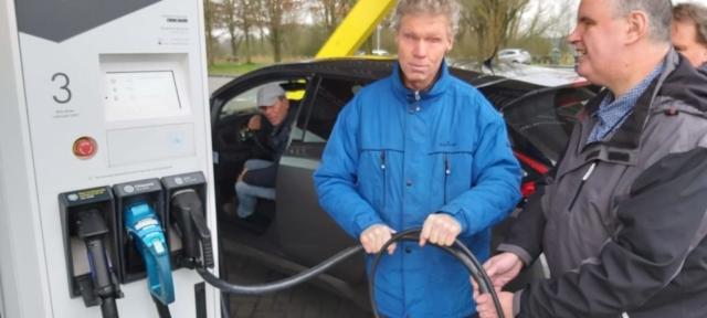 De mannen voelen hoe de elektrische auto wordt opgeladen