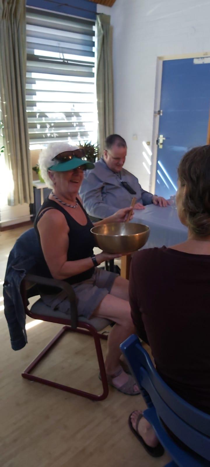Anneke ervaart de klank van de grootste klankschaal die Mareen heeft meegebracht. Dat is een klankschaal waarvan het geluid kan doordringen tot aan het bekken.