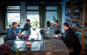 Henk, Richard, Annelie en Huug zitten rondom de tafel