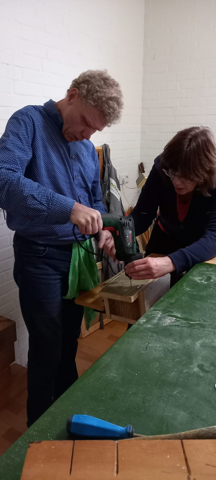 Met behulp van Annelie zet Henk de schroeven vast met de boormachine