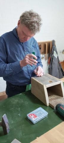 Henk probeert met de schroevendraaier de schroeven vast te zetten, maar de schroevendraaier schiet steeds van de schroef af