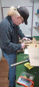 Richard is hard aan het werk om het doosje te maken voor het spelletje 'Duvel op'